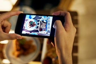 Taking smartphone photo of a dinner plate social media concept