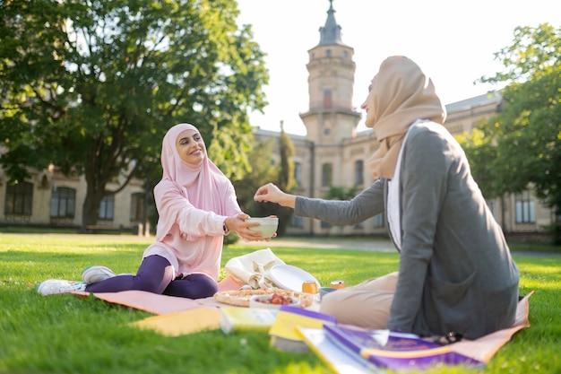 열매 좀 먹어. 친구와 점심을 먹는 동안 약간의 열매를 복용 히잡을 입고 이슬람 여성