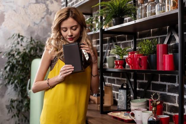 お茶を飲んでいます。ブロンドの髪のスリムな魅力的なガール フレンドがキッチンでお茶を飲みながらブレスレットを着ている