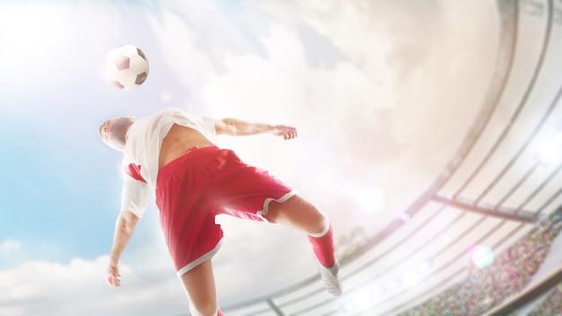 サッカーで胸にボールを持っていきます。クローズアップ。サッカー選手は胸でサッカーボールを打つことにジャンプしています。スポーツアクション。魚眼レンズ。晴れた日
