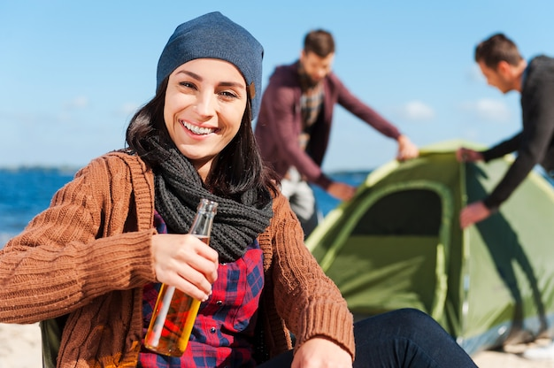 Taking time to relax. beautiful young woman holding bottle with beer and smiling while two men setting up tent in the background