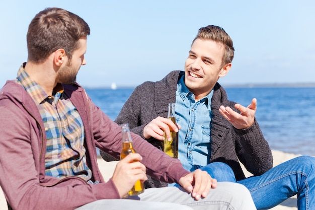 Taking time to talk with friend. two handsome young men drinking beer and talking to each other while sitting on the beach together