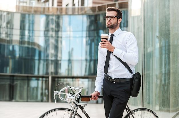 今朝を楽しむ時間を取っています。コーヒーを飲みながら、オフィスビルを背景に自転車に寄りかかって目をそらしている思いやりのある青年実業家