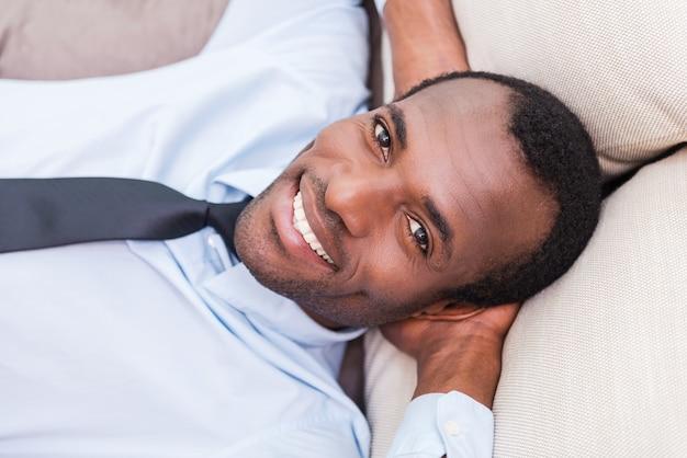 잠시 쉬는 시간을 가집니다. 셔츠와 넥타이에 잘 생긴 젊은 아프리카 남자의 상위 뷰