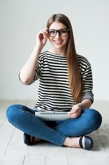 リラックスする時間を取っています。床に座って笑顔の縞模様の服を着た美しい若い女性