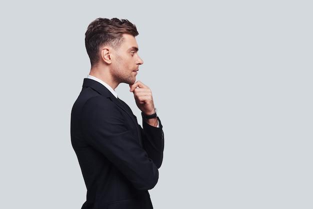 時間をかけて考える。あごに手を保ち、灰色の背景に立っている間目をそらしている完全なスーツの真面目な若い男