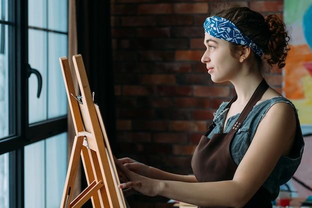 才能と創造性。抽象芸術作品を描くためにイーゼルを使用してインスピレーションを得た女性アーティストの側面図。