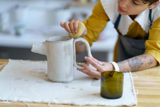 워크샵 스튜디오에서 원시 점토에서 세라믹 주전자를 성형하는 도자기 예술가 여성의 재능 있는 장인