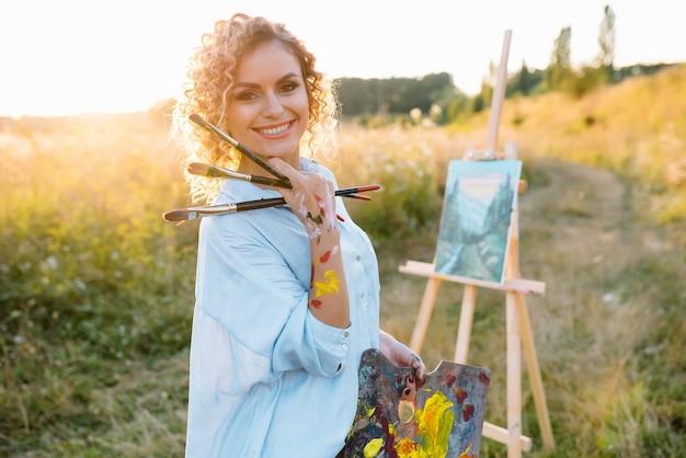 屋外の才能あるアーティストは、ブラシを持って彼女の新しいプロジェクトのために絵の具を混ぜています。