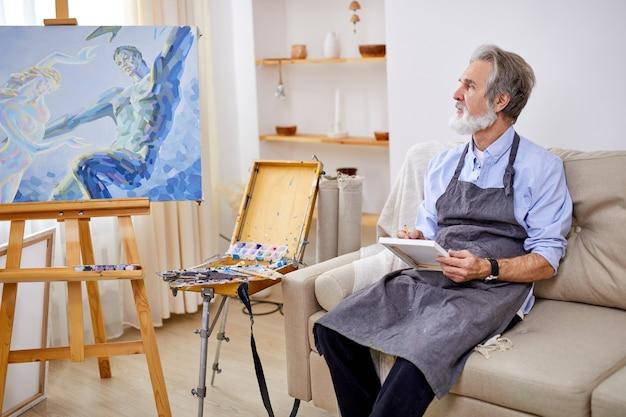 재능있는 예술가가 소파에 앉아 생각하고 연필과 종이를 손에 들고 측면을보고