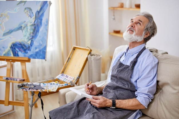 Talented artist sitting on sofa and thinking, holding pencil and paper in hands, looking up