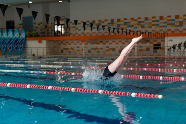 Талантливый спортсмен прыгает в бассейне, полный кадр