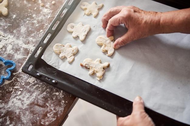 Talented baker putting shaped dough onto baking sheet