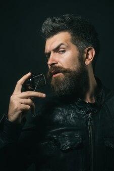 Талантливый бородатый певец с микрофоном, рок-звезда, мужчина с длинной бородой и усами в черной коже