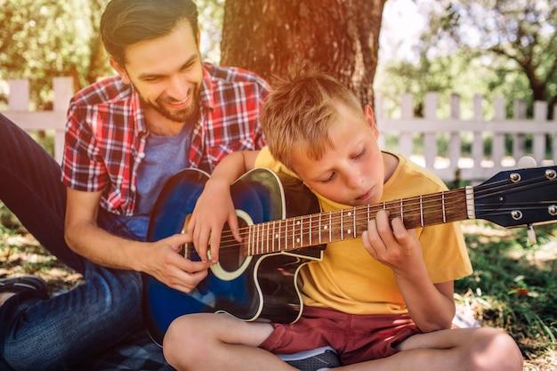 Талантливый мальчик смотрит на струны и играет на гитаре. его отец сидит рядом с ним и помогает ему. взрослый улыбается.
