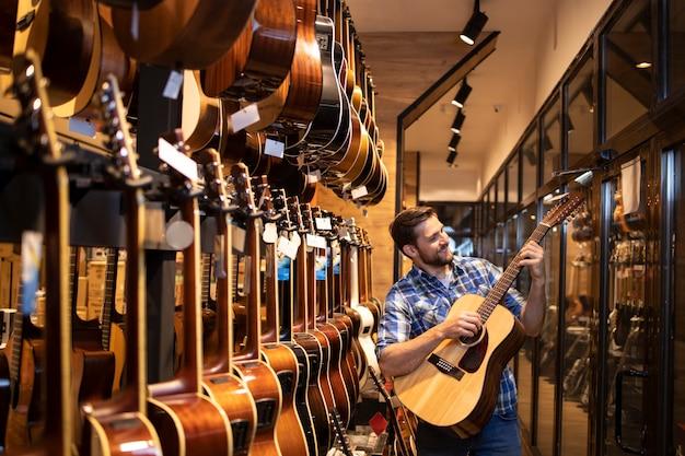 Талантливый кавказский музыкант проверяет звук нового гитарного инструмента в музыкальном магазине.