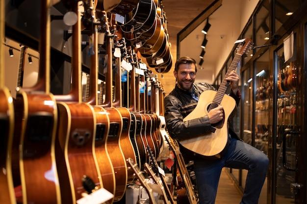 Талантливый кавказский музыкант наслаждается новой гитарой в музыкальном магазине.