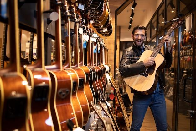 Талантливый кавказский музыкант в кожаной куртке проверяет и тестирует новый гитарный инструмент, который хочет купить в музыкальном магазине.