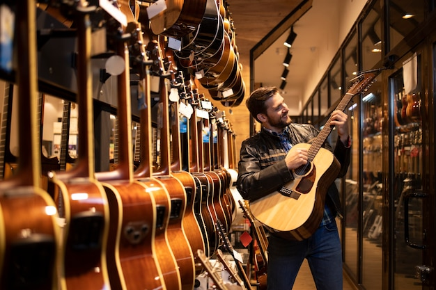 Талантливый кавказский музыкант в кожаной куртке проверяет звук нового гитарного инструмента в музыкальном магазине.