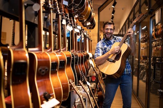 Талантливый кавказский музыкант играет и тестирует новый гитарный инструмент в музыкальном магазине.