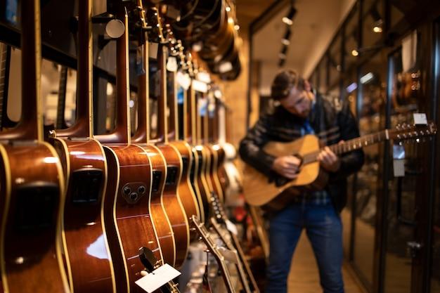 Талантливый кавказский музыкант играет на новой гитаре в музыкальном магазине и тестирует ее перед покупкой.