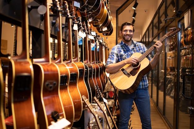 Талантливый кавказский музыкант тестирует новый гитарный инструмент в музыкальном магазине.