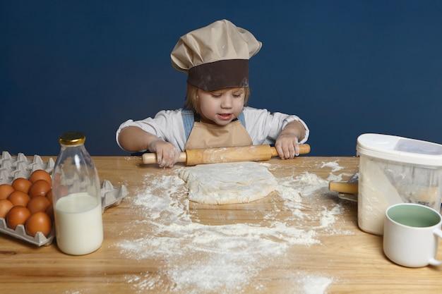 Талантливая очаровательная маленькая девочка в шляпе и фартуке шеф-повара с помощью скалки замешивает тесто для домашней пиццы. концепция детства