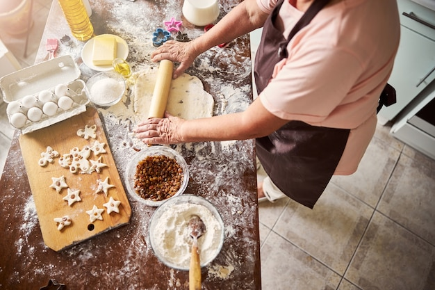 Talented cook making a flat sheet of dough