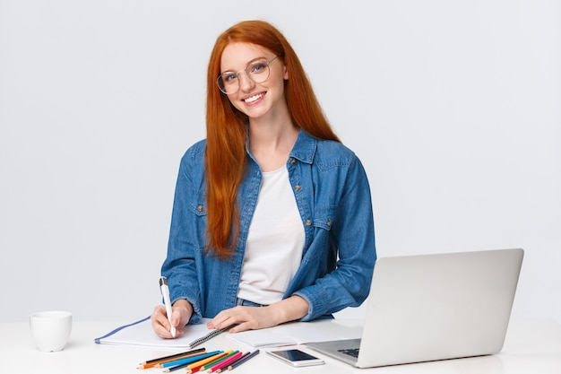 Talented creative female designer working over new project, prepare drawings for art class, standing near table, taking notes, use laptop and colored pencils, white wall
