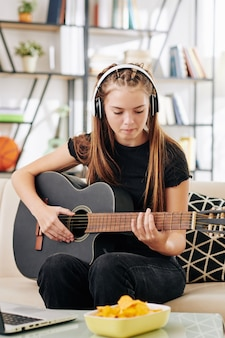 Talented creative teenage girl in headphones sitting on sofa in front of opened laptop and playing guitar