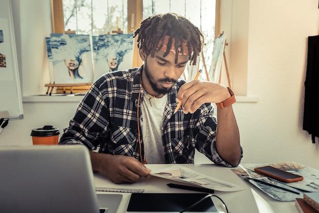 才能のあるデザイナー。彼の絵画スタジオに座ってスケッチを描くプロの才能のあるインテリアデザイナー