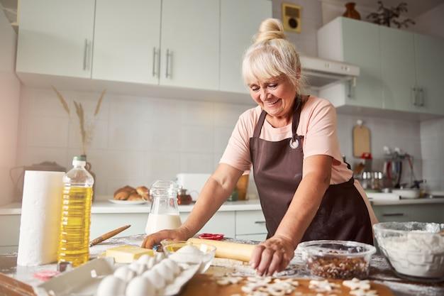 쿠키용 반죽을 준비하는 유능한 여성 제빵사