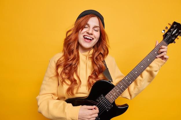 재능있는 여성 뮤지션이 일렉트릭 기타를 부르며 좋아하는 노래를 부르며 무대에서 공연을 준비하고 모자를 쓰고 스웨트 셔츠에 긴 빨간 머리를 가짐