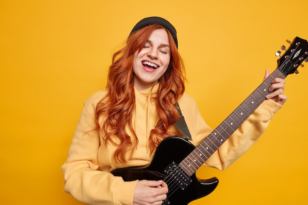 Talented female musician plays electric guitar sings favorite song prepares for performance on stage wears hat and sweatshirt has long red hair