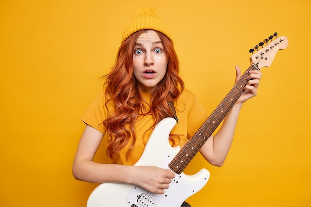 Talented female musician with natural red hair looks shocked, plays white electric guitar wears basic t shirt and hat reacts on something surprising