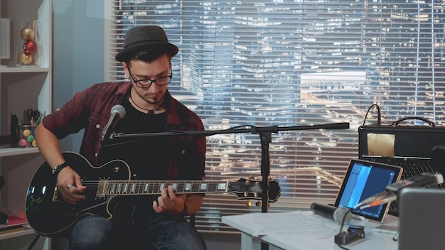 Талантливый гитарист в шляпке и модной повседневной одежде играет на гитаре и поет в домашней студии звукозаписи