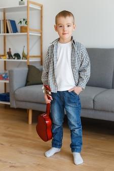 여가에서 기타를 배우는 유치원 소년 집에서 소프라노 우쿨렐레를 들고 재능있는 아이