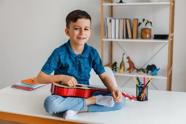 책상에 앉아 소프라노 우쿨렐레를 연주하는 재능있는 아이. 레저에서 기타를 배우는 유치원 소년. 유아 교육 및 음악 취미의 개념