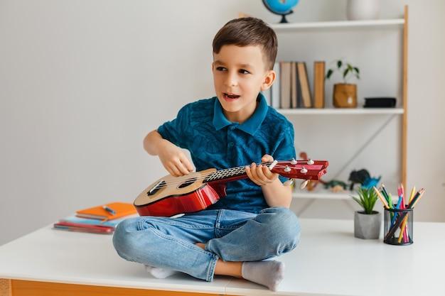 여가에서 기타를 배우는 유치원 소년 책상에 앉아 소프라노 우쿨렐레를 연주하는 재능있는 아이