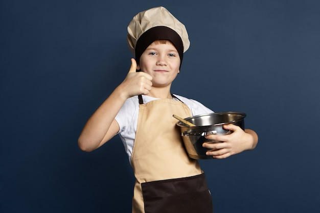 Talented little boy chef in cap and apron holding big metal saucepan, smiling confidently, showing thumbs up gesture while cooking delicious meal. food, cuisine, cookery and gastronomy concept