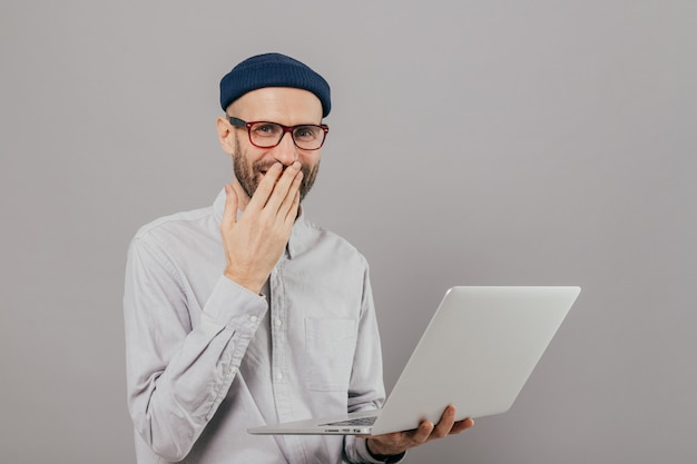 Talented male graphic designer works remotely on gadget, laughs positively, covers mouth with palm