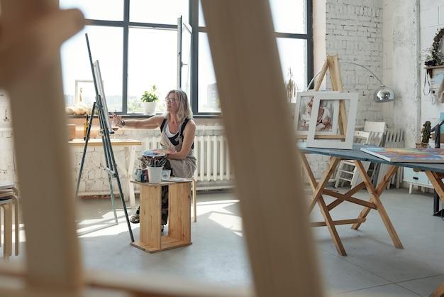 アートスタジオで写真に取り組んでいる間パレットを使用して才能のある成熟した女性アーティスト