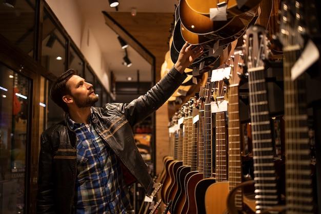 Талантливый музыкант в кожаной куртке ищет идеальную гитару в музыкальном магазине.