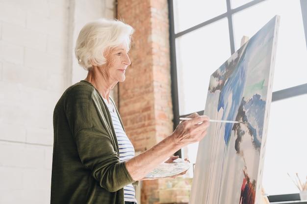 Talented senior woman painting in art studio
