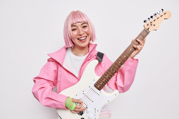 Talented stylish female musician plays electric guitar sings song enjoys rock music wears fashionable clothes feels happy