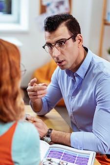 Талантливый педагог. красивый серьезный мужчина разговаривает со своей ученицей, объясняя ей новое правило