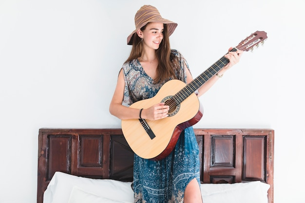 Talented teenage girl standing on bed playing guitar