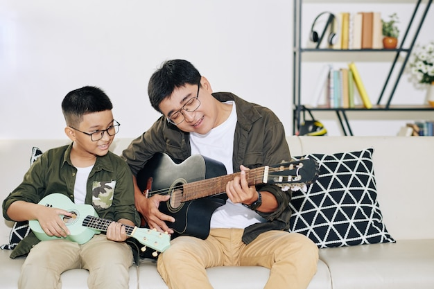 Talented vietnamese preteen boy with ukulele looking at his father playing guitar and signing
