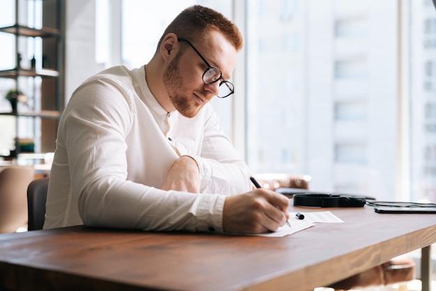 Талантливый молодой композитор в стильных очках пишет ноты ручкой на нотах