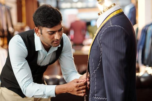 マネキンのオーダーメイドのスーツに取り組み、巻尺でパーツを測定する才能のある若いインドの仕立て屋
